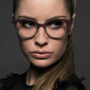Lady wearing gold and wood eyeglasses